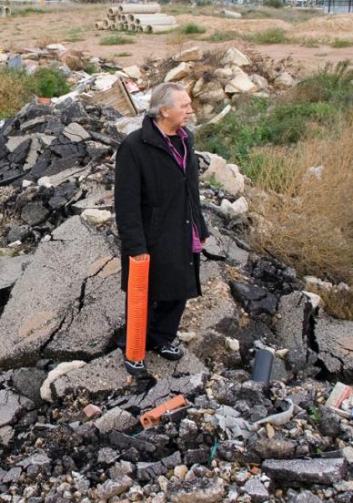 Jimmie Durham debout sur les gravats d'une route défoncée.