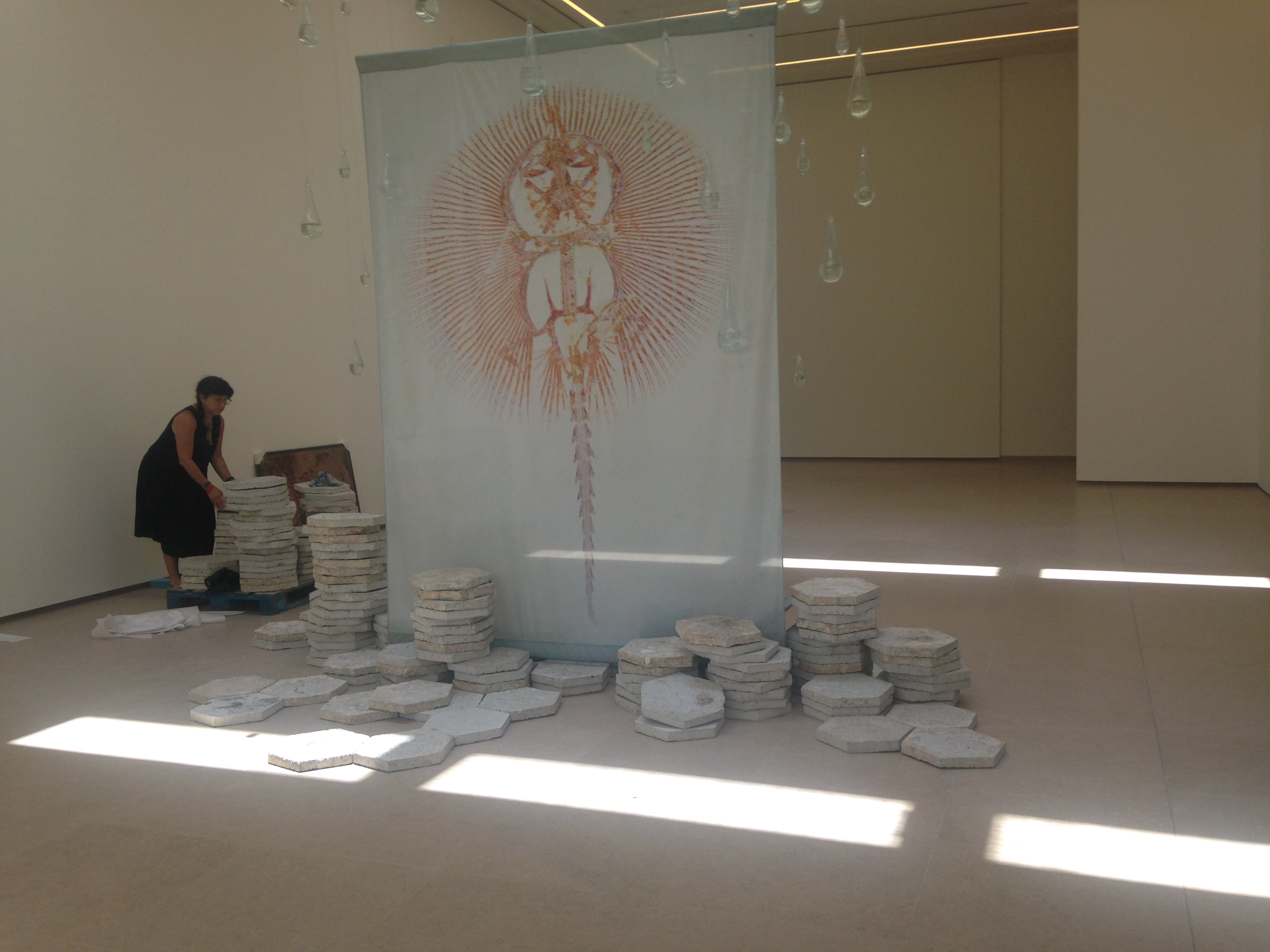 Claire Pentecost installing her work Amor Fati, 2016 (consisting of polluted water from Lebanese sources, hand-blown glass, tiles made of recycled paper, printed banner with an image of the fossil of cyclobatis), at the exhibition Let's Talk about the Weather at the Sursock Museum, Beirut. Photo by Natasa Petresin Bachelez.