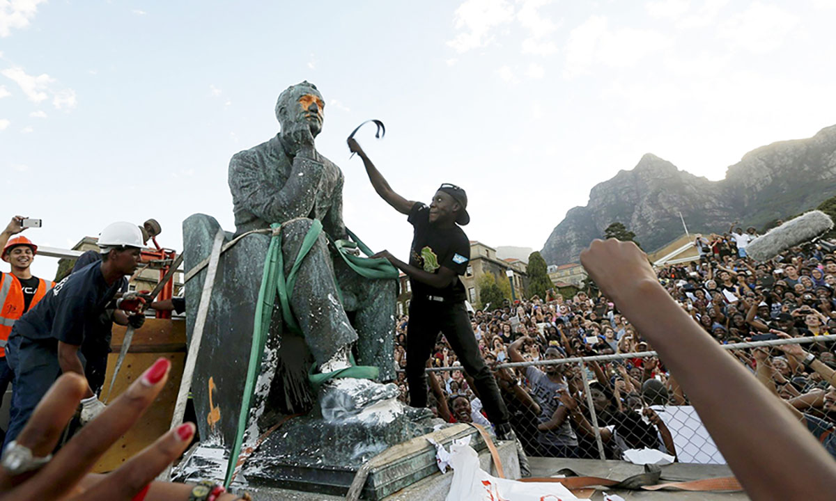 Students attacking Cecil Rhodes's statue in Cap, South Africa – the statue will be finally removed – April 2015. Image: Mike Hutchings.